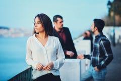 Dziewczyny piękni stojaki na moscie przy zmierzchem i spojrzeniami w odległość przeciw niebieskiemu niebu i wieczór miastu Młoda  Fotografia Stock