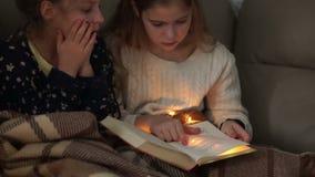 Dziewczyny piżamy przyjęcia Siostry czytają książkę i dyskutują ich zawartość Bożonarodzeniowe Światła zbiory
