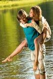 Dziewczyny piggyback jedzie jego chłopaka w wodzie Zdjęcie Stock