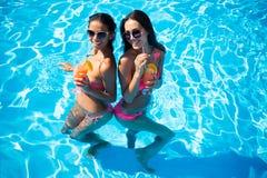 Dziewczyny pije koktajle w pływackim basenie Fotografia Stock