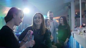 Dziewczyny plotkują przy klubem i piją koktajle za zakazują kontuar na tle światła zbiory wideo