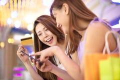 Dziewczyny pokazuje kredytową kartę i ogląda telefon w robi zakupy mal Zdjęcia Royalty Free