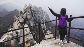 Dziewczyny pozycja na znaku w pięknych górach fotografia stock