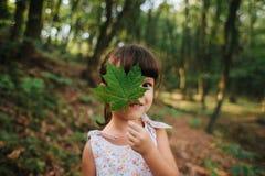 Dziewczyny pozycja w drewnach trzyma liść w jego ręki chowany b obraz stock