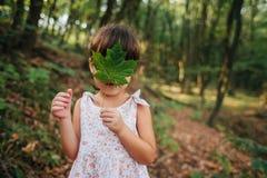 Dziewczyny pozycja w drewnach trzyma liść w jego ręki chowany b obraz royalty free