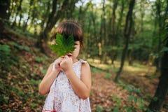 Dziewczyny pozycja w drewnach trzyma liść w jego ręki chowany b zdjęcia stock
