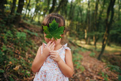Dziewczyny pozycja w drewnach trzyma liść w jego ręki chowany b fotografia stock