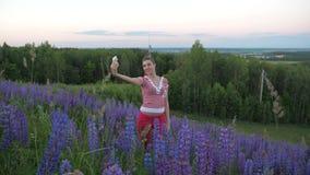 Dziewczyny pozycja w polu purpury kwitnie robić selfie na smartphone zbiory wideo
