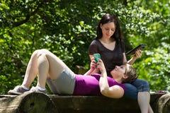 Dziewczyny przy parkowym używa smartphone i pastylką horyzontalnymi, zdjęcia stock