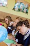 Dziewczyny przy szkolnymi biurkami Obrazy Royalty Free