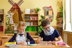 Dziewczyny przy szkolnymi biurkami Zdjęcia Stock