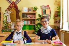 Dziewczyny przy szkolnymi biurkami Fotografia Royalty Free
