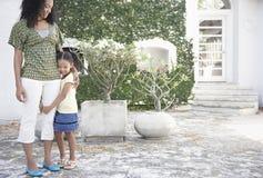 Dziewczyny przytulenia matki noga W jardzie zdjęcia royalty free