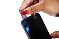 Dziewczyny ręka wkłada mikro SD kartę w telefonu komórkowego smartphone Obrazy Stock