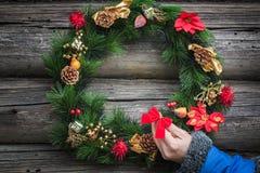 Dziewczyny ręka z błękit kurtki ciepłym rękawem dekoruje świątecznego Bożenarodzeniowego wianek obrazy stock