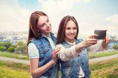 Dziewczyny robią selfie, pejzaż miejski na tle Obraz Stock