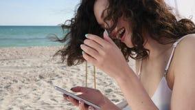 Dziewczyny rozmowa w ogólnospołecznych sieciach na plaży, uśmiechnięty kobiet uses telefon komórkowy na oceanu wybrzeżu, młoda ko zbiory wideo