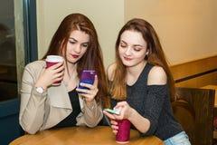 Dziewczyny są przyglądające ich smartphones zdjęcie stock