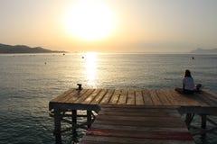 Dziewczyny słuchająca muzyka i zegarka wschód słońca od doku Obrazy Royalty Free