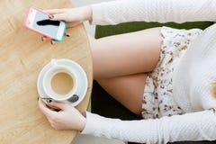 Dziewczyny ` s nogi, filiżanka kawy i telefon komórkowy, Zdjęcia Stock