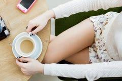 Dziewczyny ` s nogi, filiżanka kawy i telefon komórkowy, Obraz Royalty Free