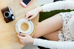 Dziewczyny ` s nogi, filiżanka kawy i telefon komórkowy, Zdjęcie Royalty Free