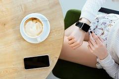 Dziewczyny ` s nogi, filiżanka kawy, zegarek i telefon komórkowy, Zdjęcie Stock