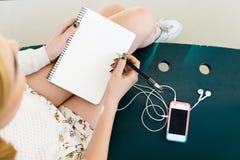 Dziewczyny ` s nogi, pisze w notatniku, telefon komórkowy Obrazy Royalty Free