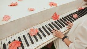 Dziewczyny ` s ręki na klawiaturze pianino Liście klonowi rozpraszający na kluczach autumn buty deszczowej podlegających gumowego zbiory wideo