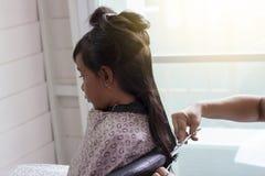Dziewczyny siedzący ostrzyżenie fryzjerem zdjęcie stock