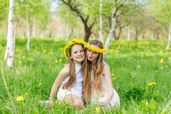 Dziewczyny siedzą w trawie z wiankami dandelions Zdjęcie Stock