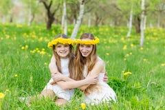 Dziewczyny siedzą w trawie z wiankami dandelions Obrazy Stock
