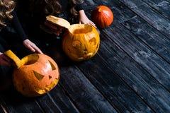 Dziewczyny siedzi z Halloweenową banią przewodzą dźwigarka lampion na da zdjęcie royalty free