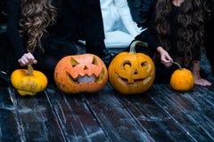 Dziewczyny siedzi z Halloweenową banią przewodzą dźwigarka lampion na da obraz stock