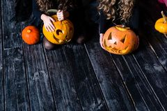 Dziewczyny siedzi z Halloweenową banią przewodzą dźwigarka lampion na da fotografia stock