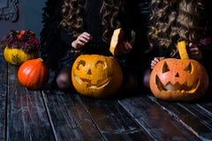 Dziewczyny siedzi z Halloweenową banią przewodzą dźwigarka lampion na da obrazy stock
