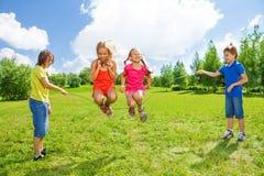 Dziewczyny skacze nad arkaną z przyjaciółmi Fotografia Royalty Free
