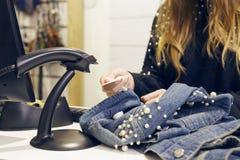 Dziewczyny skanerowania barcode od drelichowej kurtki obraz royalty free