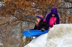 Dziewczyny sledding na wzgórzu Fotografia Stock