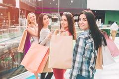Dziewczyny stoją i pozują Są przyglądający backwards i ono uśmiecha się Trzymają torby na ich ramionach zdjęcie royalty free