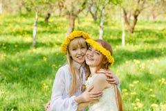 Dziewczyny stoją z wiankami dandelions na ich hea Zdjęcia Royalty Free