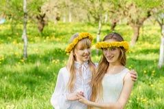 Dziewczyny stoją z wiankami dandelions na ich hea Obraz Royalty Free