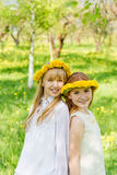 Dziewczyny stoją z wiankami dandelions na ich hea Obraz Stock