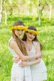 Dziewczyny stoją z wiankami dandelions na ich hea Zdjęcie Stock