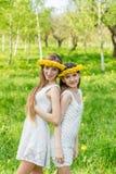 Dziewczyny stoją z wiankami dandelions na ich hea Zdjęcie Royalty Free