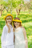 Dziewczyny stoją z wiankami dandelions na ich hea Fotografia Royalty Free