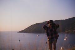 Dziewczyny stojaki na krawędzi falezy blisko patrzeć słońce dolinę, morza i oceanu lub Kobieta cieszy się zmierzch lub Fotografia Royalty Free