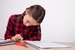 Dziewczyny studiowanie koncentrujący używać kalkulatora na nauka stole zdjęcia stock