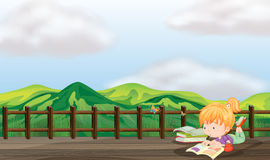 Dziewczyny studiowanie przy drewnianym mostem Obrazy Royalty Free