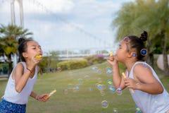 Dziewczyny szczęścia śmieszny mydlany bąbel w parku, Śmia się szczęśliwych wi fotografia royalty free